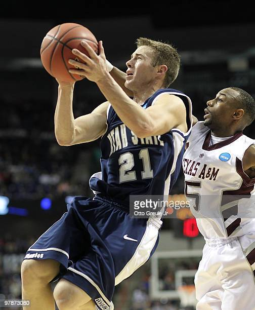 Jared Quayle of the Utah State Aggies shoots against Dash Harris of the Texas AM Aggies during the first round of the 2010 NCAA men's basketball...
