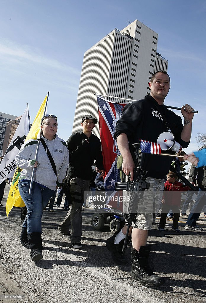 Jared Robertson, right, Amber Deckart, left, and gun rights supporters walk up State Street to a gun rights rally at the Utah State Capitol on March 2, 2013 in Salt Lake City, Utah. The rally attracted several hundred people for the march to the Utah Capitol in favor of 2nd Amendment rights as gun control supporters call for more limits and bans on assault weapons.