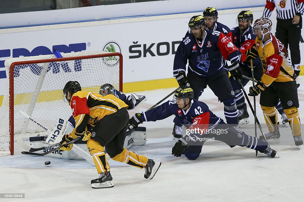 Jared Ross (#42 ERC Ingolstadt) - Spina Dave #12 yellow SAI takes a shot on goal - Goalie Timo Pielmeier (#51 ERC Ingolstadt) - Game 2 of 6 during the Champions Hockey League group stage game between ERC Ingolstadt and SaiPa Lappeenranta on August 23, 2014 in Ingolstadt, Germany.