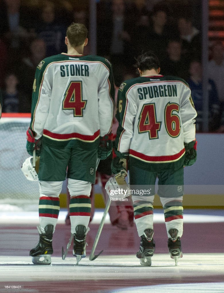 Jared Spurgeon #46 and Clayton Stoner #4 of the Minnesota Wild observe the singing of the national anthems prior to NHL action against the Vancouver Canucks on March 18, 2013 at Rogers Arena in Vancouver, British Columbia, Canada.