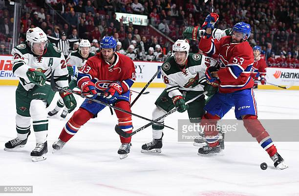 Jared Spurgeon and Ryan Suter of the Minnesota Wild defend against Mike Brown and Lucas Lessio of the Montreal Canadiens in the NHL game at the Bell...