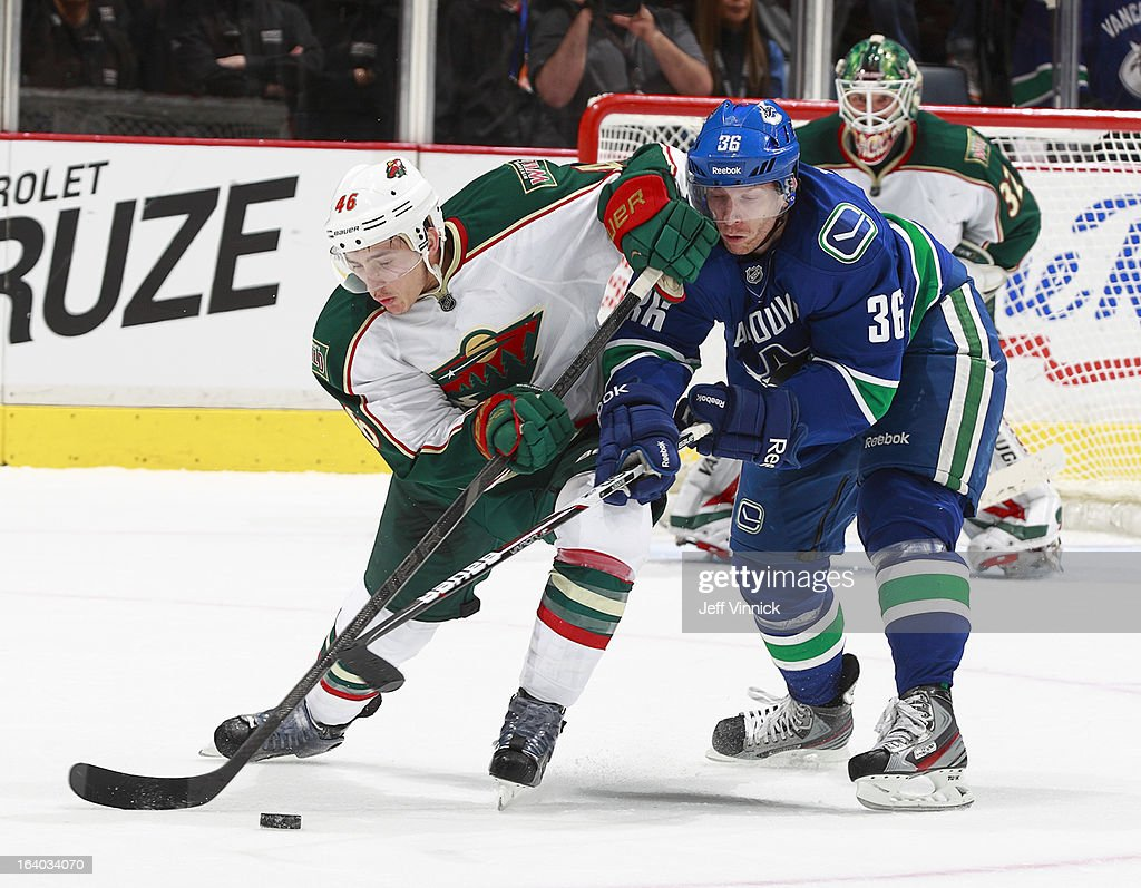 Jared Spurgeon #46 of the Minnesota Wild and Jannik Hansen #36 of the Vancouver Canucks battle for the puck during their NHL game at Rogers Arena March 18, 2013 in Vancouver, British Columbia, Canada.