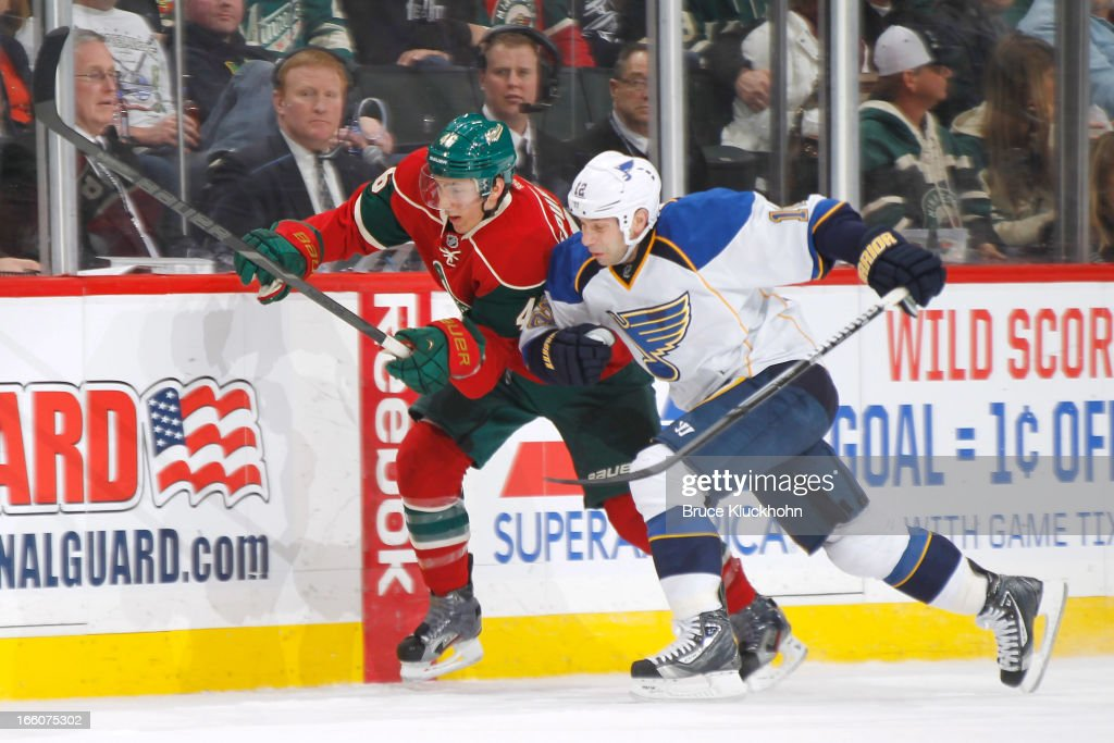 Jared Spurgeon of the Minnesota Wild and Scott Nichol of the St Louis Blues skate to the puck during the game on April 1 2013 at the Xcel Energy...