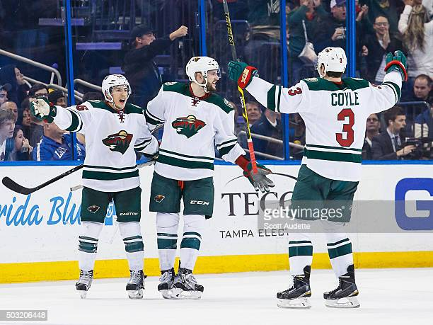 Jared Spurgeon of the Minnesota Wild celebrates his goal with teammates Marco Scandella and Charlie Coyle during the third period at the Amalie Arena...