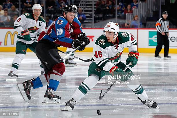 Jared Spurgeon of the Minnesota Wild controls the puck against Nathan MacKinnon of the Colorado Avalanche at Pepsi Center on October 8 2015 in Denver...