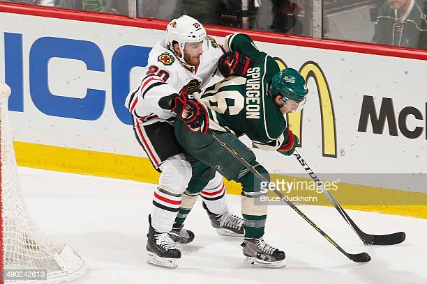 Jared Spurgeon of the Minnesota Wild handles the puck with Brandon Saad of the Chicago Blackhawks defending during Game Six of the Second Round of...