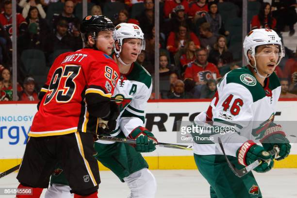 Jared Spurgeon of the Minnesota Wild looks for a pass while Sam Bennett of the Calgary Flames and Ryan Suter of the Minnesota Wild battle for...
