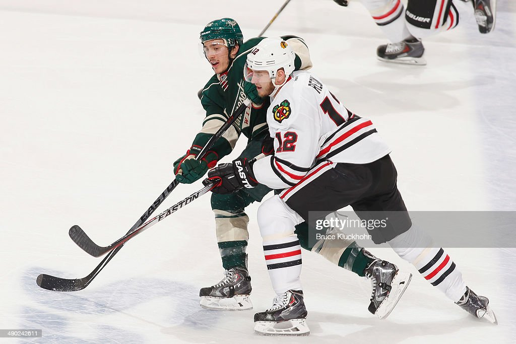 Jared Spurgeon #46 of the Minnesota Wild passes the puck with Peter Regin #12 of the Chicago Blackhawks defending during Game Six of the Second Round of the 2014 Stanley Cup Playoffs on May 13, 2014 at the Xcel Energy Center in St. Paul, Minnesota.