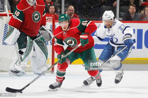 Jared Spurgeon of the Minnesota Wild skates with the puck while JT Brown of the Tampa Bay Lightning defends during the game on February 10 2017 at...