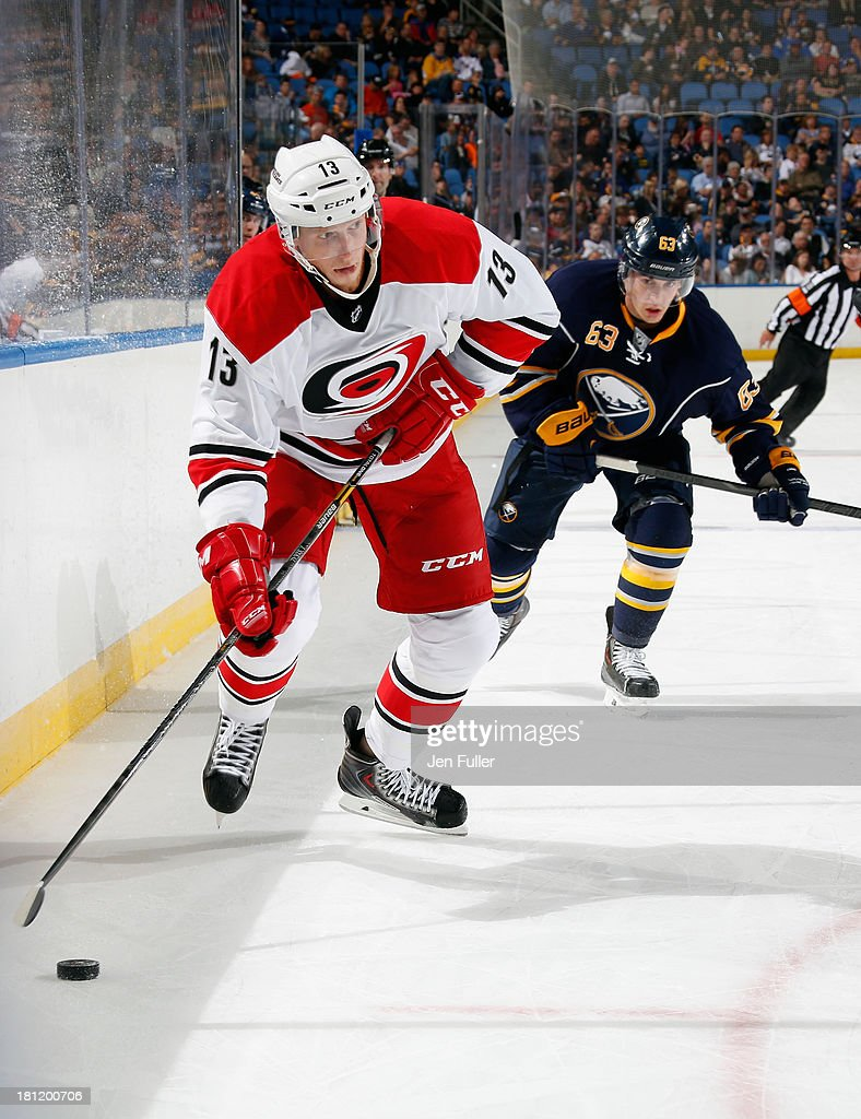 Jared Staal #13 of the Carolina Hurricanes skates up ice as he is chased by <a gi-track='captionPersonalityLinkClicked' href=/galleries/search?phrase=Tyler+Ennis+-+Ice+Hockey+Player&family=editorial&specificpeople=4754184 ng-click='$event.stopPropagation()'>Tyler Ennis</a> #63 of the Buffalo Sabres in a preseason game at First Niagara Center on September 19, 2013 in Buffalo, United States.
