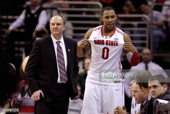 Jared Sullinger of the Ohio State Buckeyes holds his jersey out as head coach Thad Matta looks on late in the game against the TexasSan Antonio...