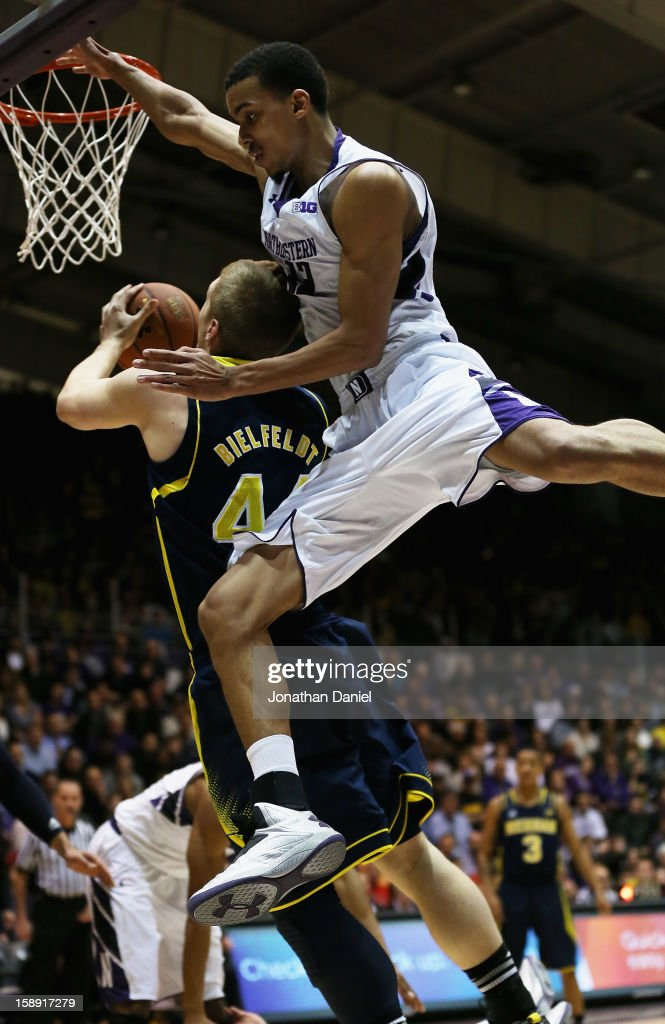 Jared Swopshire #12 of the Northwestern Wildcats fouls Max Bielfeldt #44 of the Michigan Wolverines at Welsh-Ryan Arena on January 3, 2013 in Evanston, Illinois.