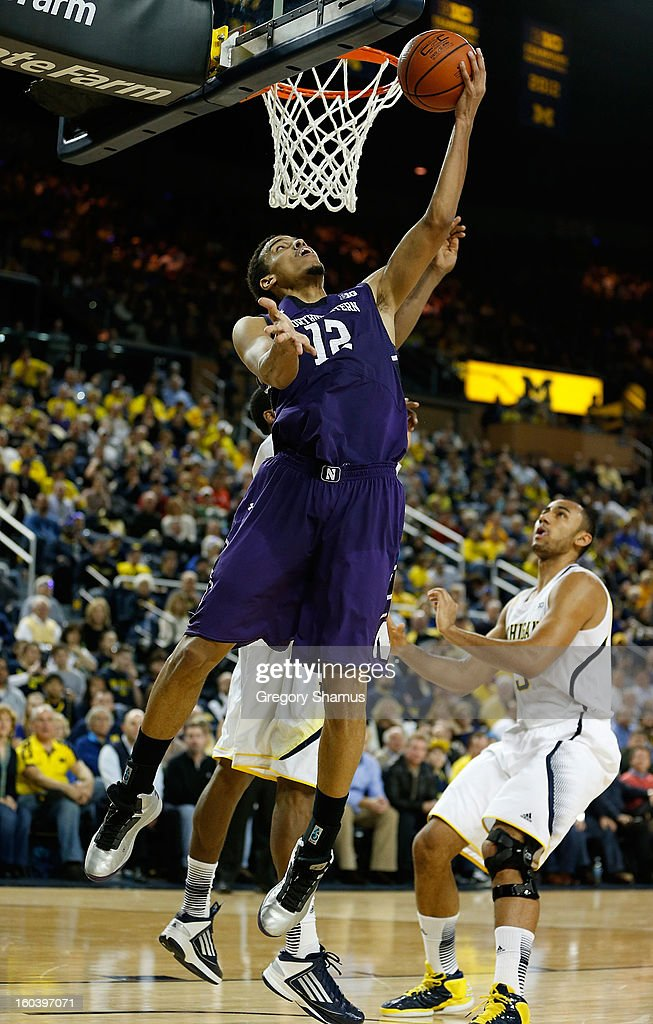 Jared Swopshire #12 of the Northwestern Wildcats gets to the basket for a second half layup next to Trey Burke #3 of the Michigan Wolverines at Crisler Center on January 30, 2013 in Ann Arbor, Michigan. Michigan won the game 68-46.