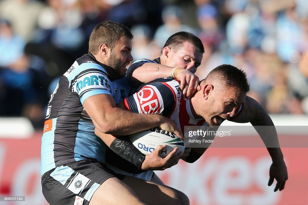 Jared Waerea-Hargreaves of the Roosters is tackled by Paul Gallen and Wade Graham of the Sharks during the round 17 NRL match between the Sydney Roosters and the Cronulla Sharks at Central Coast Stadium on July 1, 2017 in Gosford, Australia.