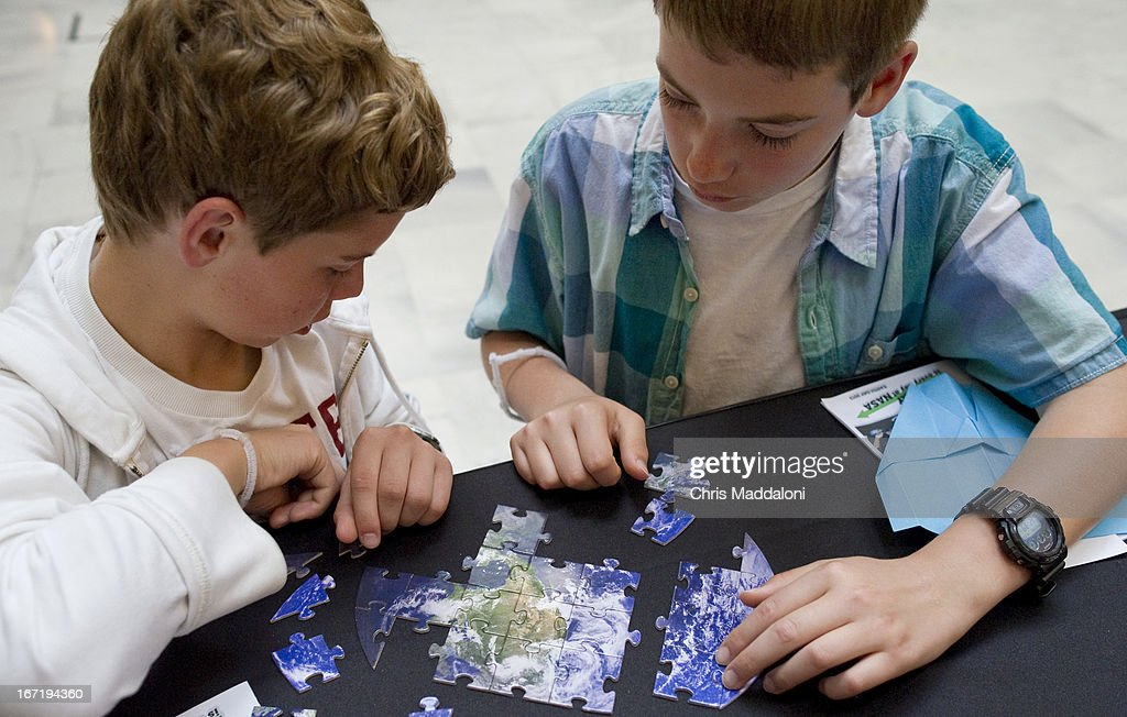 Jaret Williams, 13, and Sam Rivera, 13, from St. Mary's County, MD., work on a Earth puzzle at the NASA booth at an Earth Day 2013 celebration at Union Station.
