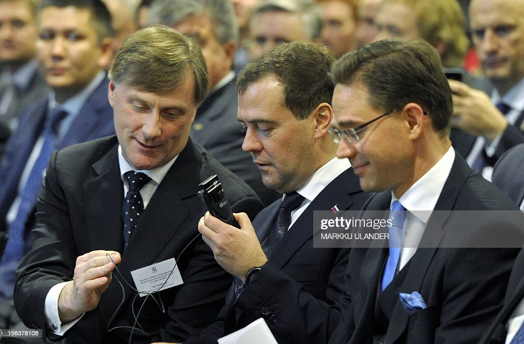 Jari Koskinen Finnish Agriculture Minister helps Russian Prime Minister Dmitri Medvedev adjust his headphones as they attend with Finnish Prime Minister Jyrki Katainen the Forest Summit Helsinki, Finland on November 14, 2012 in Helsinki, Finland.