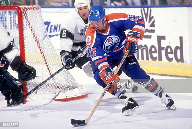 Jari Kurri of the Edmonton Oilers controls the puck as he and Dean Kennedy of the Los Angeles Kings round the net during an NHL game circa 1989 at...