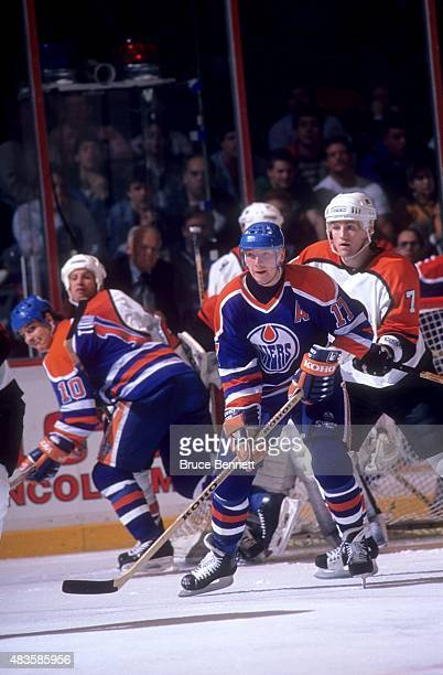 Jari Kurri of the Edmonton Oilers follows the play as Jay Wells of the Philadelphia Flyers defends on November 24 1989 at the Spectrum in...