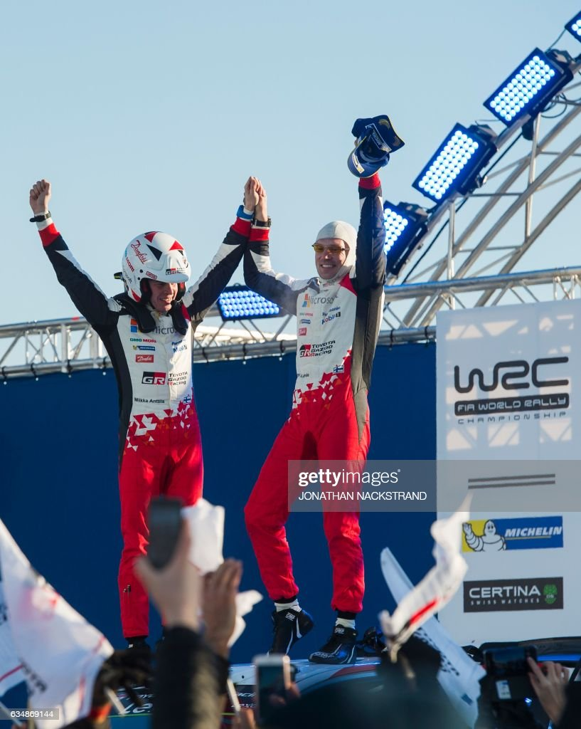 Jari Matti Latvala (R) of Finland and his co-driver Miikka Anttila stand on their Toyota Yaris WRC after winning the Rally Sweden, second round of the FIA World Rally Championship on February 12, 2017 in Torsby, Sweden. / AFP / Jonathan NACKSTRAND