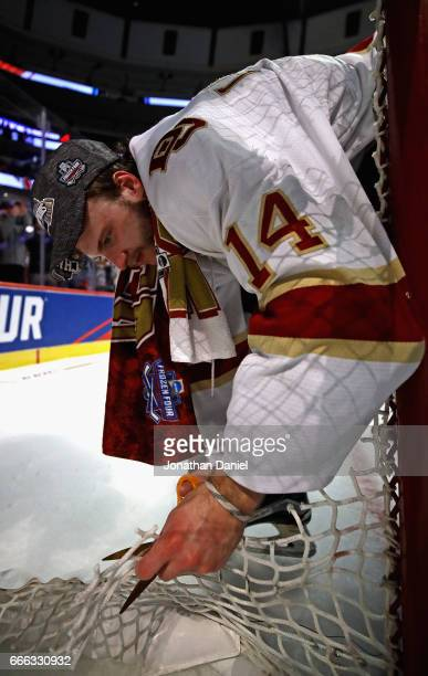 Jarid Lukosevicius of the Denver Pioneers cuts a piece of the net follwoing a win over the MinnesotaDuluth Bulldogs during the 2017 NCAA Division I...