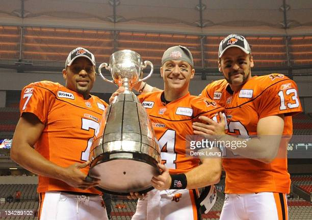 Jarious Jackson Travis Lulay and Mike Reilly of the BC Lions hold the Grey Cup trophy after defeating the Winnipeg Blue Bombers during the Grey Cup...