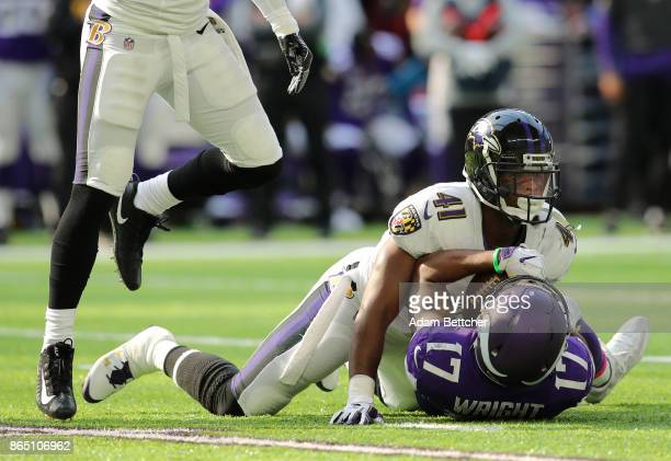 Jarius Wright of the Minnesota Vikings is tacked with the ball by defender Anthony Levine of the Baltimore Ravens in the second quarter of the game...
