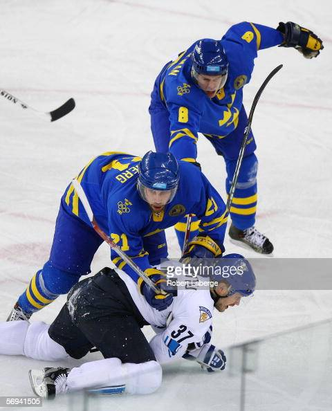 Jarkko Ruutu of Finland is pushed to the ice by Peter Forsberg and Christian Backman of Sweden during the final of the men's ice hockey match during...