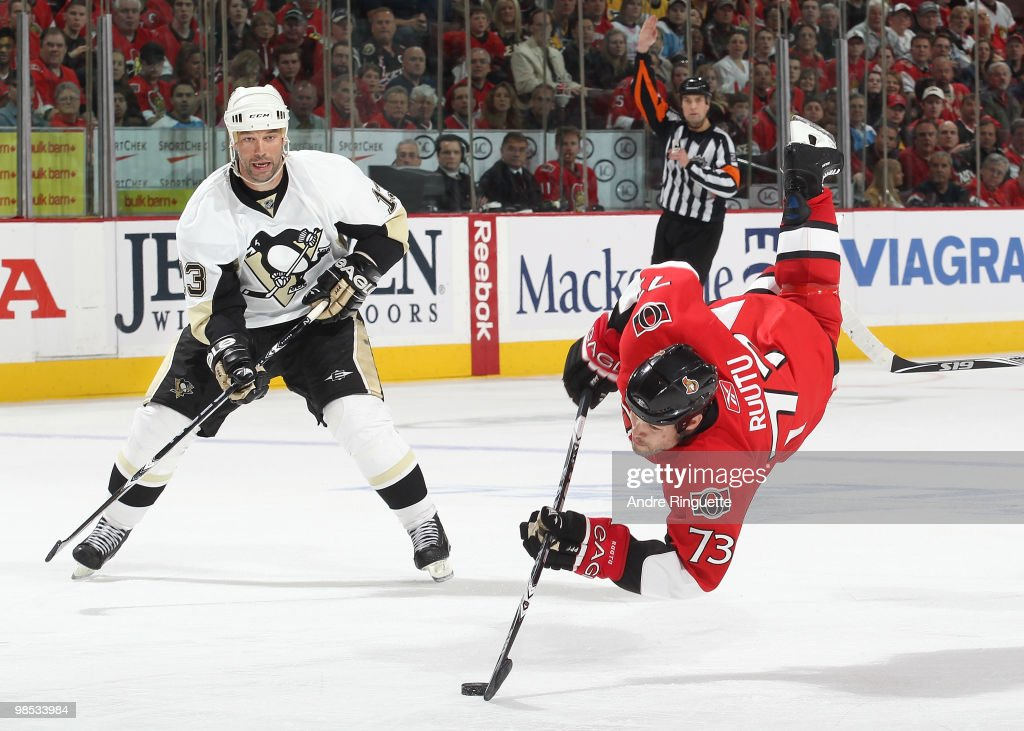 Jarkko Ruutu of the Ottawa Senators goes airborne while stickhandling the puck after being tripped as Bill Guerin of the Pittsburgh Penguins looks on...