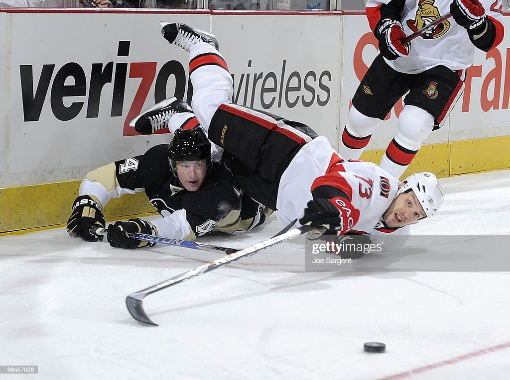 Jarkko Ruutu of the Ottawa Senators reaches for the loose puck after colliding with Jordan Leopold of the Pittsburgh Penguins in Game One of the...