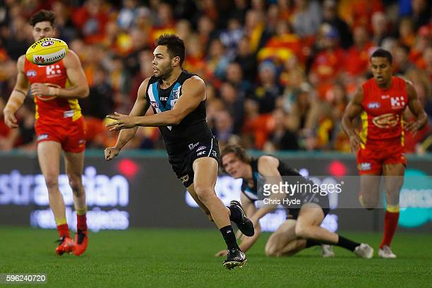 Jarman Impey of the Power handballs during the round 23 AFL match between the Gold Coast Suns and the Port Adelaide Power at Metricon Stadium on...