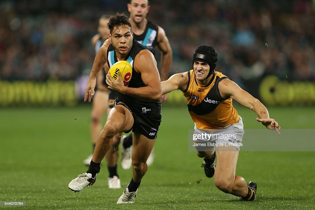 Jarman Impey of the Power is tackled by Ben Griffiths of the Tigers during the 2016 AFL Round 15 match between Port Adelaide Power and the Richmond Tigers at Adelaide Oval on July 1, 2016 in Adelaide, Australia.