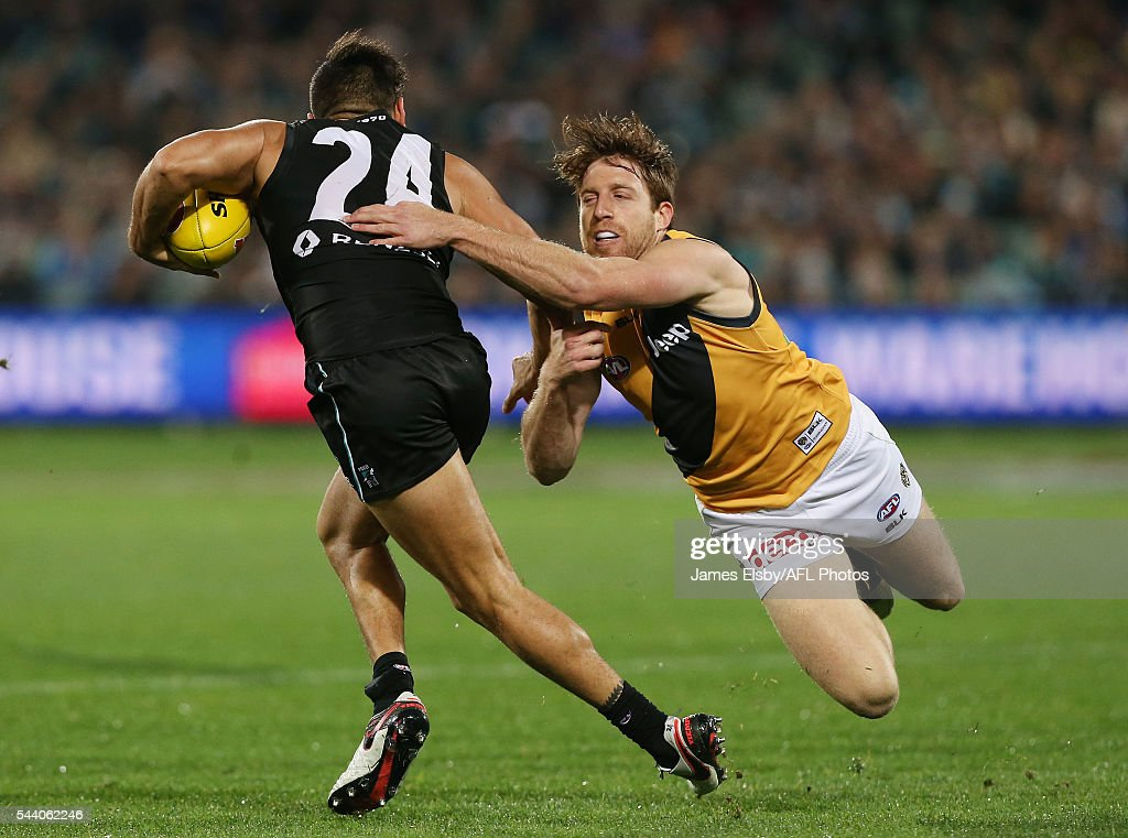 Jarman Impey of the Power is tackled by Reece Conca of the Tigers during the 2016 AFL Round 15 match between Port Adelaide Power and the Richmond Tigers at Adelaide Oval on July 1, 2016 in Adelaide, Australia.