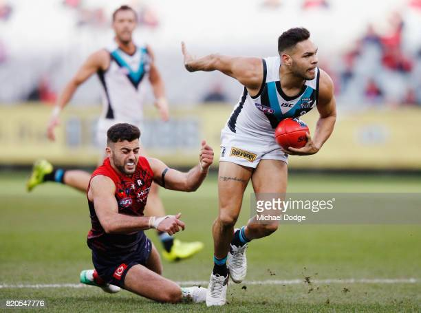 Jarman Impey of the Power runs with the ball away from Christian Salem of the Demons during the round 18 AFL match between the Melbourne Demons and...