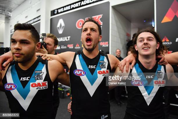 Jarman Impey Travis Boak and Darcy ByrneJones of the Power sing the club song after defeationg the Magpies during the round 21 AFL match between Port...