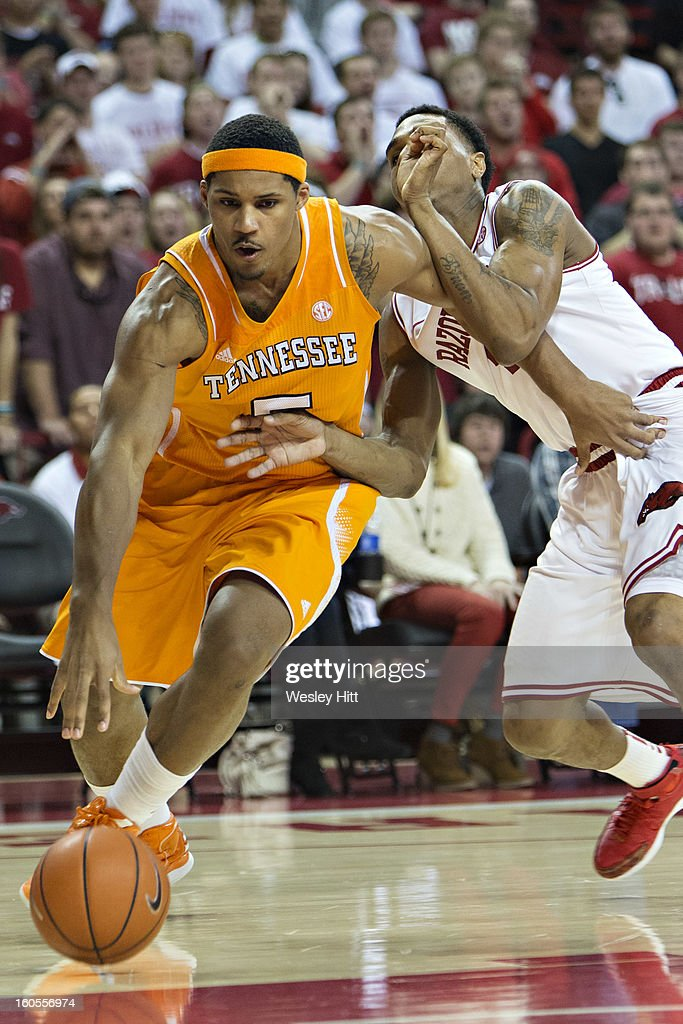 Jarnell Stokes #5 of the Tennessee Volunteers dribbles around Coty Clarke #4 of the Arkansas Razorbacks at Bud Walton Arena on February 2, 2013 in Fayetteville, Arkansas. The Razorbacks defeated the Volunteers 73-60.