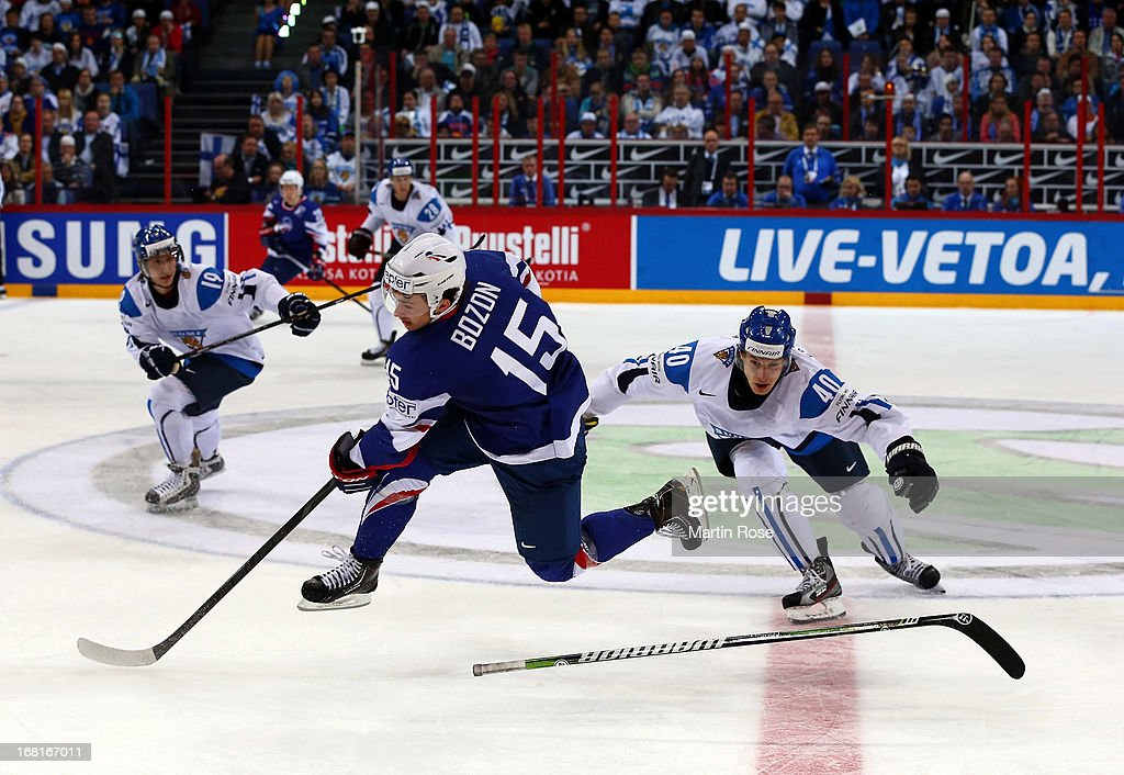 Jarno Koskiranta (R) of Finland and Tim Bozon (L) of France battle for the puck during the IIHF World Championship group H match between Finland and France at Hartwall Areena on May 6, 2013 in Helsinki, Finland.