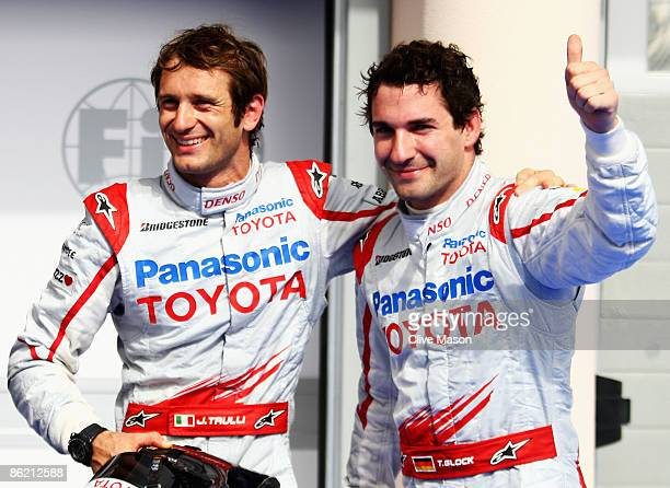 Jarno Trulli of Italy and Toyota celebrates with second placed team mate Timo Glock of Germany and Toyota in parc ferme after taking pole position...