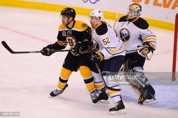 Jarome Igila of the Boston Bruins watches the play against Alexander Sulzer and Jhonas Enroth of the Buffalo Sabres at the TD Garden on December 21...