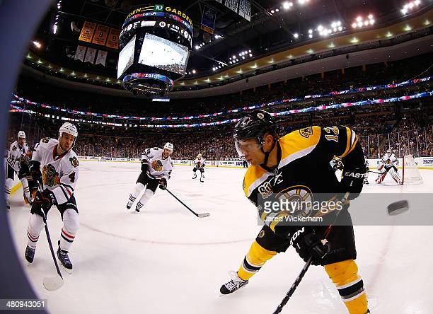 Jarome Iginla of the Boston Bruins has the puck fly by him in the corner in front of Niklas Hjalmarsson of the Chicago Blackhawks in the first period...