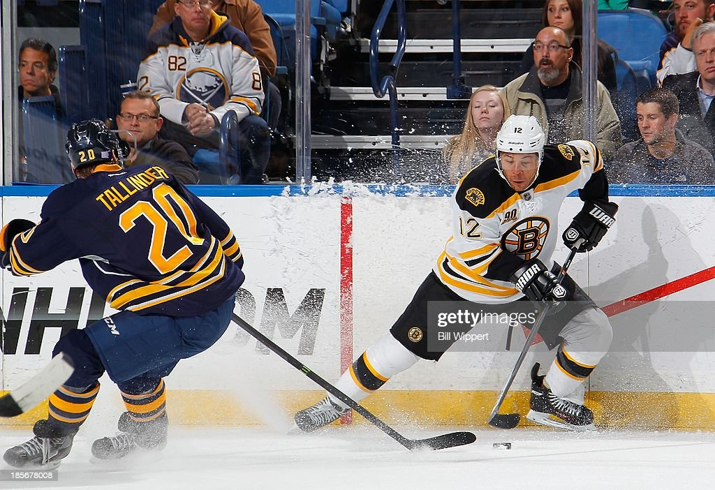 Jarome Iginla #12 of the Boston Bruins makes a quick stop with the puck in front of Henrik Tallinder #20 of the Buffalo Sabres on October 23, 2013 at the First Niagara Center in Buffalo, New York.
