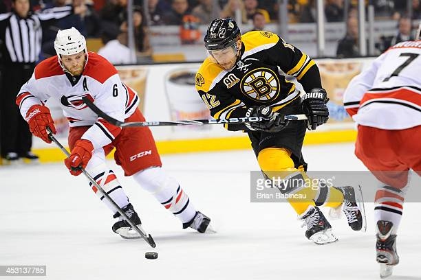 Jarome Iginla of the Boston Bruins skates after the puck against Tim Gleason of the Carolina Hurricanes at the TD Garden on November 23 2013 in...