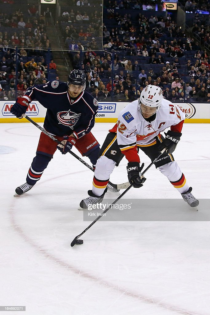 Jarome Iginla #12 of the Calgary Flames and Nick Foligno #71 of the Columbus Blue Jackets battle for control of the puck on March 22, 2013 at Nationwide Arena in Columbus, Ohio.