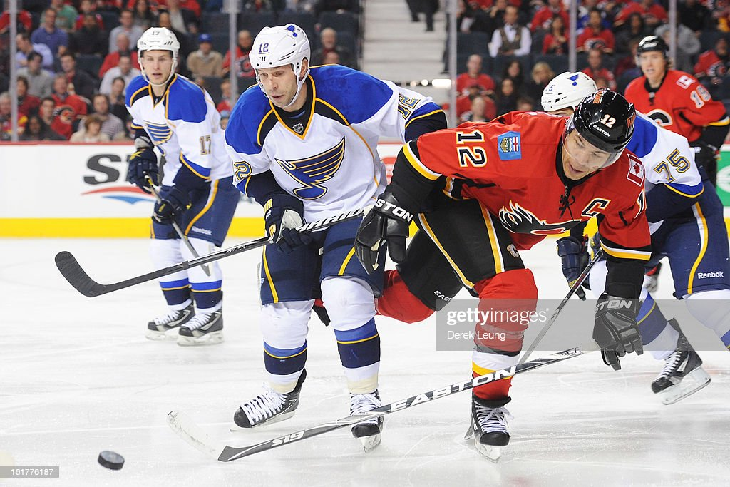 Jarome Iginla of the Calgary Flames battles for the puck with Scott Nichol of the St Louis Blues during an NHL game at Scotiabank Saddledome on...