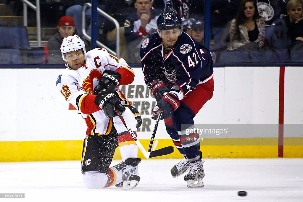 Jarome Iginla #12 of the Calgary Flames flips the puck away from Artem Ansimov #42 of the Columbus Blue Jackets during the first period on February 7, 2013 at Nationwide Arena in Columbus, Ohio.