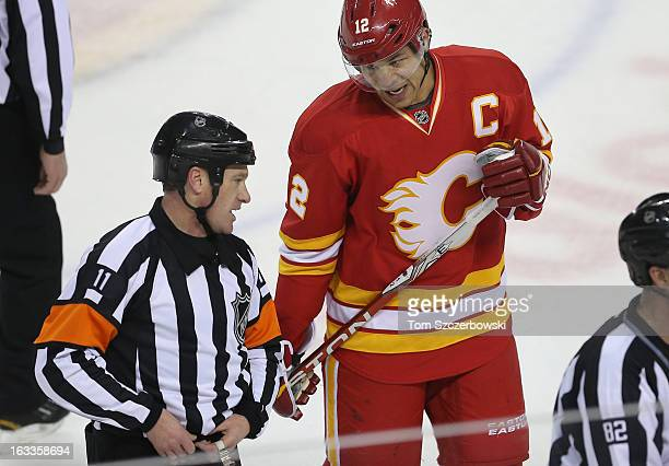 Jarome Iginla of the Calgary Flames talks to referee Kelly Sutherland during a break in the action during an NHL game against the Vancouver Canucks...