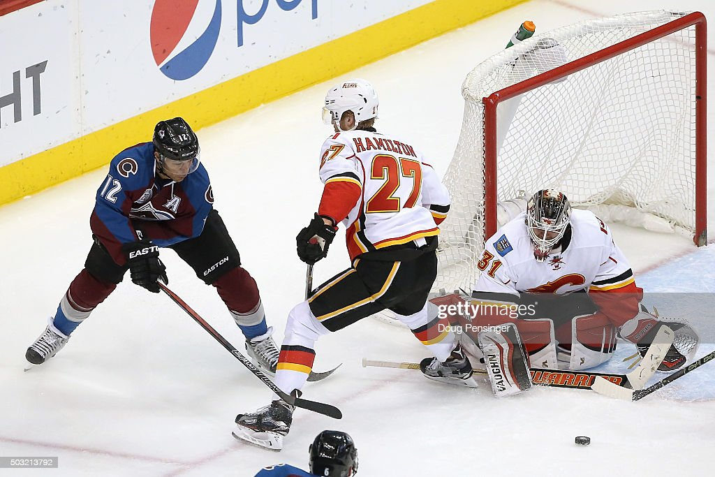 Jarome Iginla #12 of the Colorado Avalanche tries to get off a shot against Dougie Hamilton #27 of the Calgary Flames as goalie Karri Ramo #31 of the Calgary Flames defends the goal at Pepsi Center on January 2, 2016 in Denver, Colorado. The Flames defeated the Avalanche 4-0.