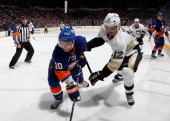 Jarome Iginla of the Pittsburgh Penguins hits Keith Aucoin of the New York Islanders in Game Three of the Eastern Conference Quarterfinals during the...