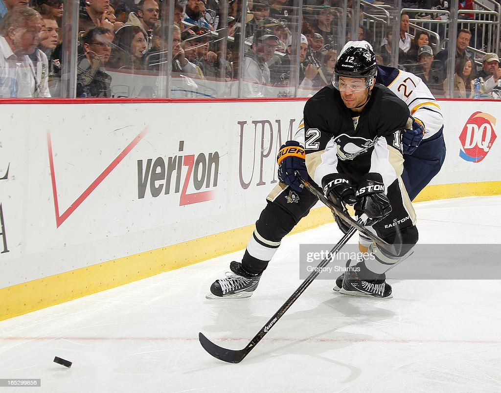 <a gi-track='captionPersonalityLinkClicked' href=/galleries/search?phrase=Jarome+Iginla&family=editorial&specificpeople=201792 ng-click='$event.stopPropagation()'>Jarome Iginla</a> #12 of the Pittsburgh Penguins skates for the loose puck in front of <a gi-track='captionPersonalityLinkClicked' href=/galleries/search?phrase=Adam+Pardy&family=editorial&specificpeople=2221762 ng-click='$event.stopPropagation()'>Adam Pardy</a> #27 of the Buffalo Sabres on April 2, 2013 at Consol Energy Center in Pittsburgh, Pennsylvania. Buffalo won the game 4-1.