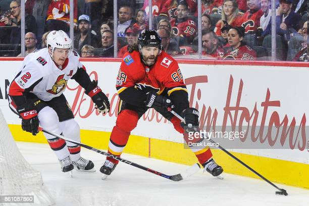 Jaromir Jagr of the Calgary Flames carries the puck against Dion Phaneuf of the Ottawa Senators during an NHL game at Scotiabank Saddledome on...