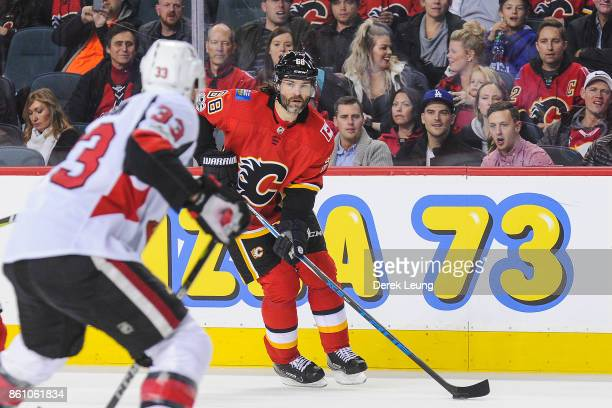 Jaromir Jagr of the Calgary Flames carries the puck as Fredrik Claesson of the Ottawa Senators defends during an NHL game at Scotiabank Saddledome on...